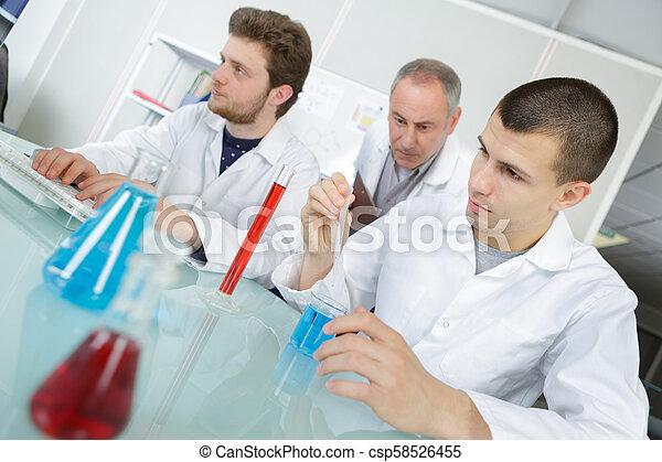 Estudiantes con maestro en clase de química - csp58526455