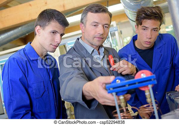 Profesor haciendo una demostración para estudiantes varones - csp52294838