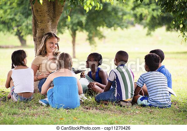 Niños y educación, maestros leyendo libros a estudiantes jóvenes - csp11270426