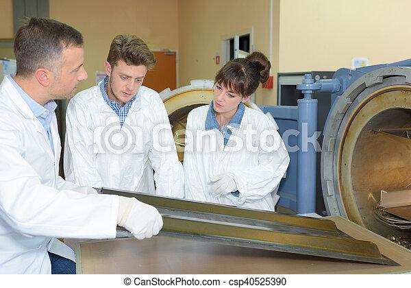 Profesor con estudiantes en el taller - csp40525390