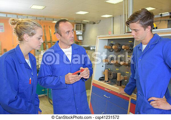 Profesor con estudiantes en el taller - csp41231572