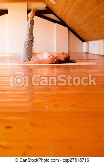 Mujer practicando yoga en un estudio - csp27818716