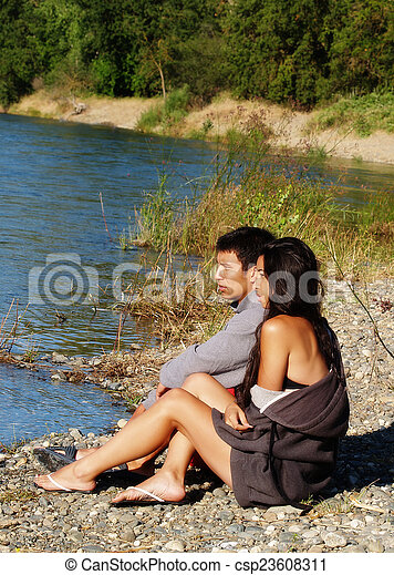Ethnic Couple Sitting Outdoors On River Bank - csp23608311