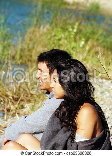 Ethnic Couple Sitting Outdoors On River Bank - csp23608328