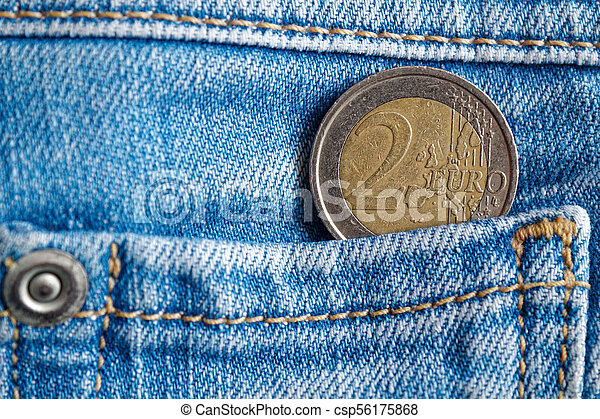 Euro coin with a denomination of 2 euro in the pocket of dark blue denim jeans - csp56175868