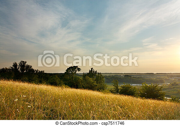Evening Landscape with cirrus clouds and magical light of the sunset over rural expanses - csp7511746