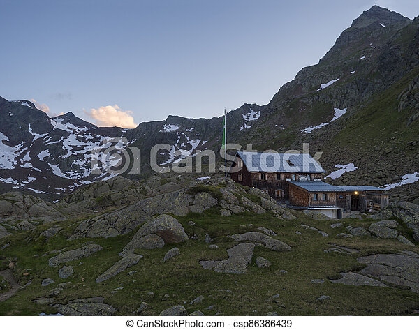 Evening sunset summer view of Bremer Hutte, an alpine mountian wooden hut with snow-capped moutain peaks, Stubai Alps, Tyrol, Austria - csp86386439