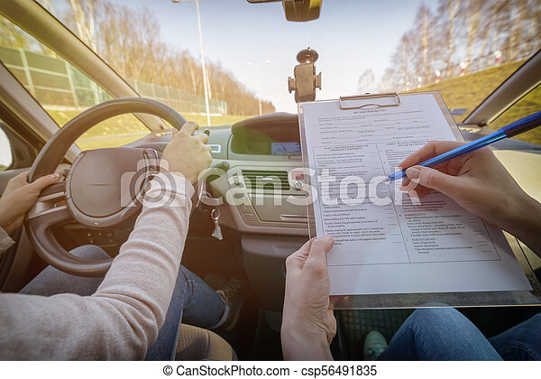 Examiner filling in driver's license road test form - csp56491835