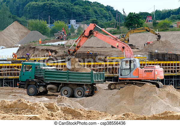 Excavator loads the ground in the truck - csp38556436
