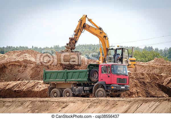 Excavator loads the ground in the truck - csp38556437
