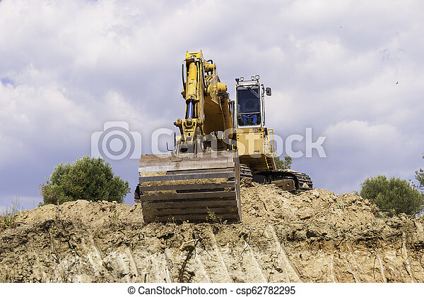 Excavator on the construction site is preparing to load the soil - csp62782295