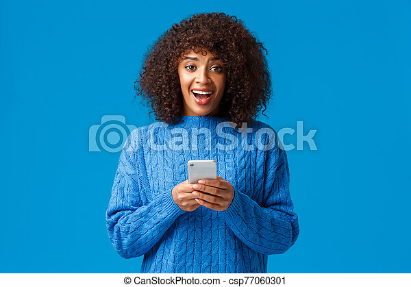 Excited and overwhelmed smiling attractive young african-american woman, wearing winter blue sweater, looking amazed and surprised camera as receive great news over smartphone message - csp77060301