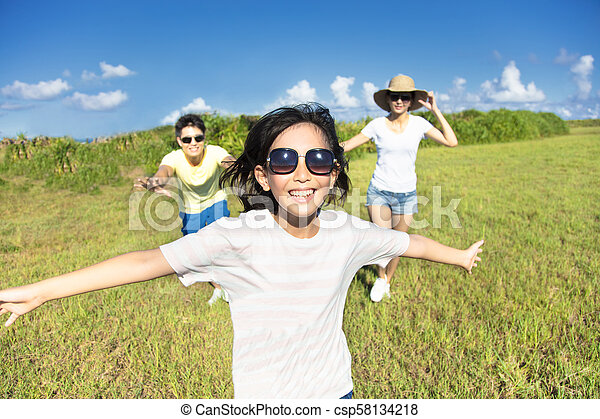 Excited happy family running on the grass - csp58134218