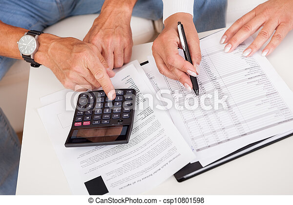 Excited middle-aged couple doing finances at home - csp10801598