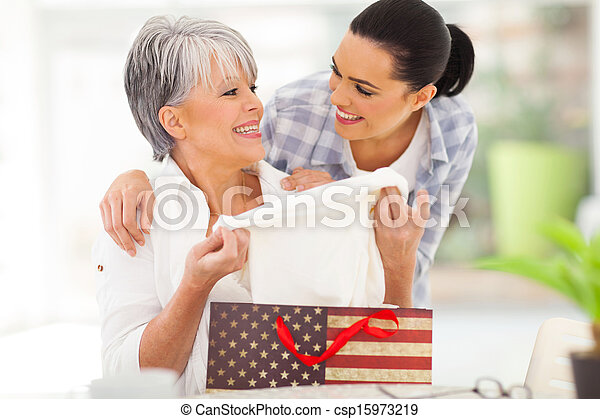 excited middle aged mother looking at her gift - csp15973219