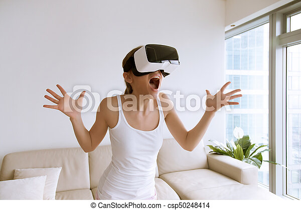 Excited woman using VR glasses for the first time - csp50248414