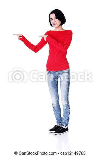Excited young woman pointing on copy space - csp12149763