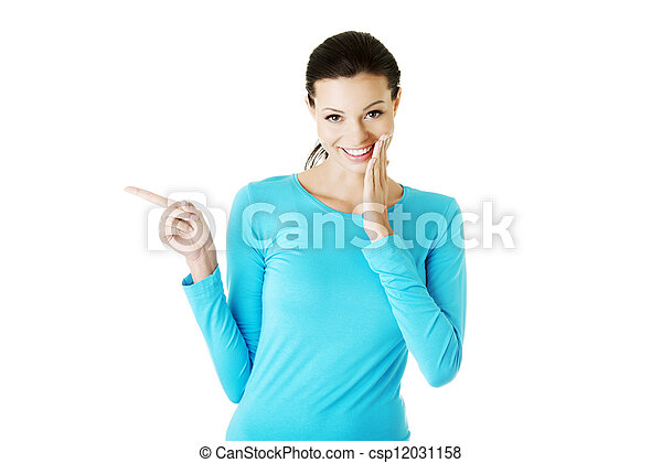 Excited young woman pointing on copy space - csp12031158