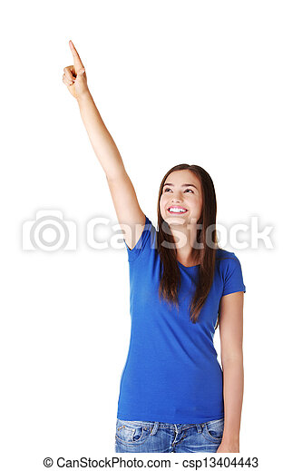 Excited young woman pointing on copy space - csp13404443
