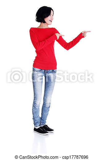 Excited young woman pointing on copy space - csp17787696
