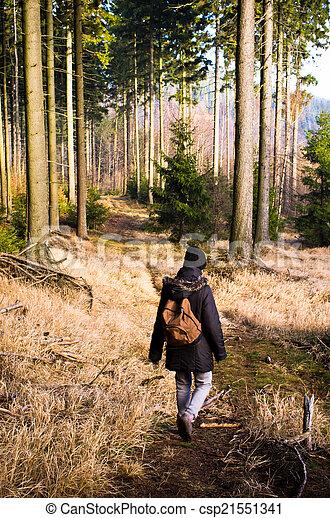 Una mujer caminando en el bosque - csp21551341