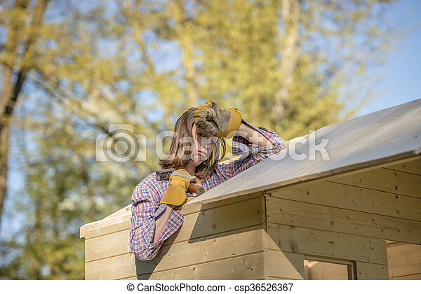 Exhuasted woman working on roof of tree house - csp36526367