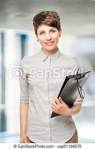 Una joven exitosa con una carpeta en la oficina - csp51194570