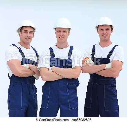 Exitosos constructores de equipos en overalls y cascos - csp58032808