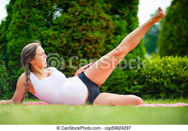 expectant woman performing side reclining leg lift on yoga