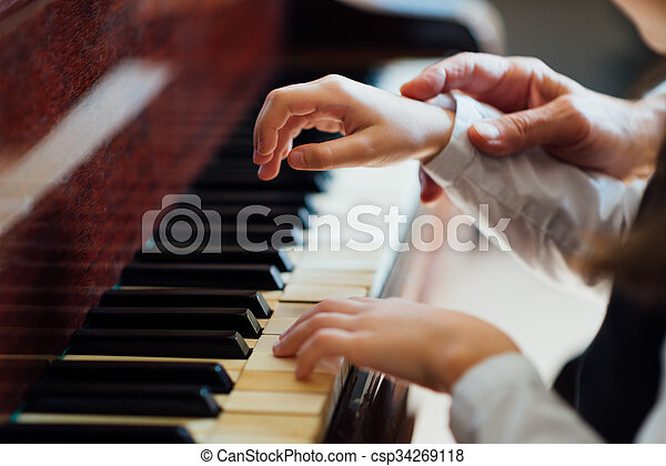 experienced master piano hand helps the student  - csp34269118