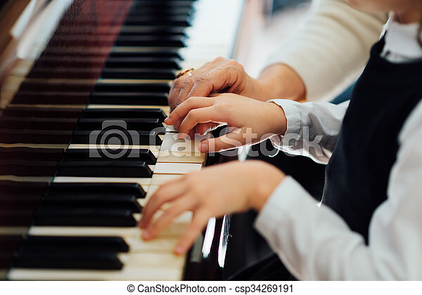 experienced master piano hand helps the student  - csp34269191