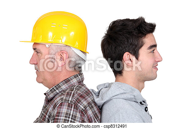 Experienced tradesman standing back to back with his new apprentice - csp8312491
