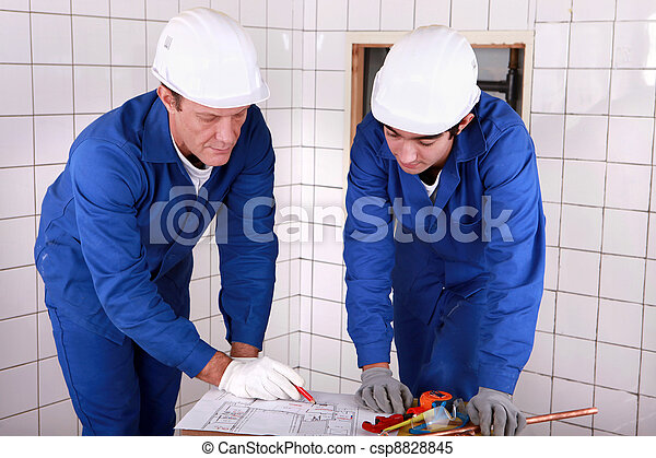 Experienced tradesman teaching his apprentice how to read a blueprint - csp8828845
