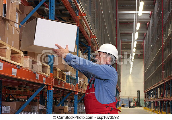experienced worker with box in warehouse - csp1673592