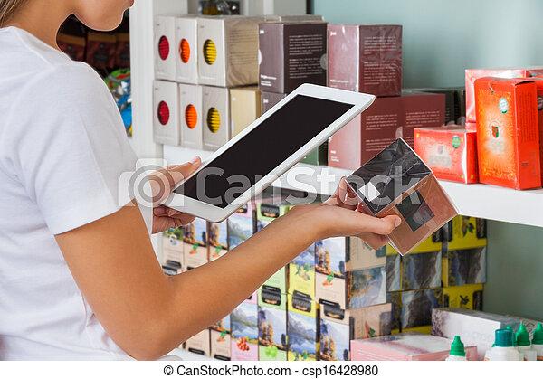Mujer escaneando código de barras a través de la tableta digital - csp16428980