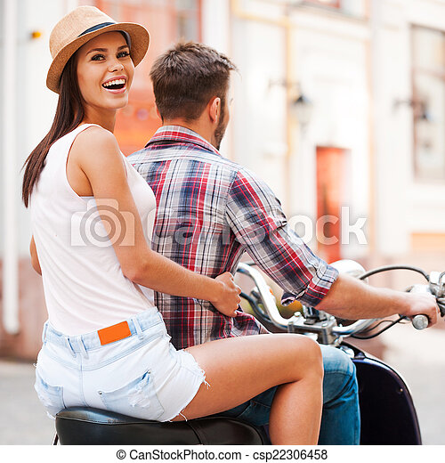 Exploring new places together. Rear view of beautiful young couple riding scooter together while beautiful woman looking over shoulder and smiling - csp22306458