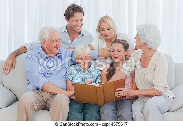Extended cheerful family looking at a photo album - csp14575617