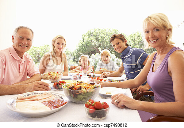 Extended family, parents, grandparents and children, eating outdoors - csp7490812