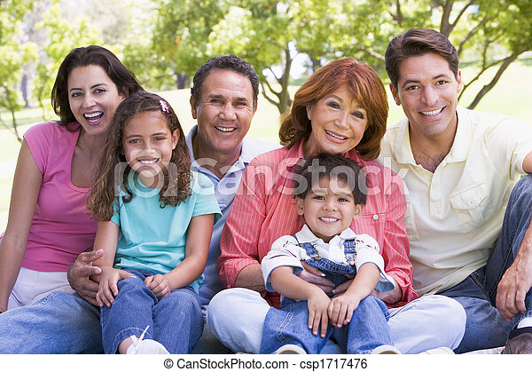 Extended family sitting outdoors smiling - csp1717476
