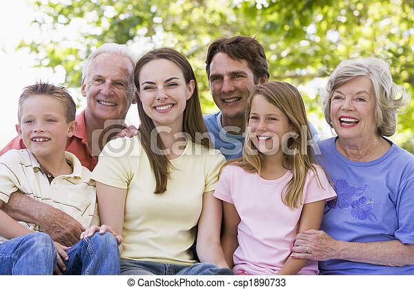 Extended family sitting outdoors smiling - csp1890733