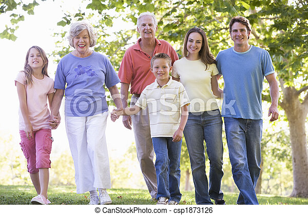 Extended family walking in park holding hands and smiling - csp1873126