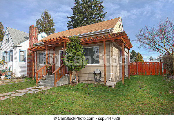 Exterior photo of small beige house - csp5447629
