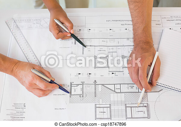 Extreme close-up of hands working on blueprints - csp18747896