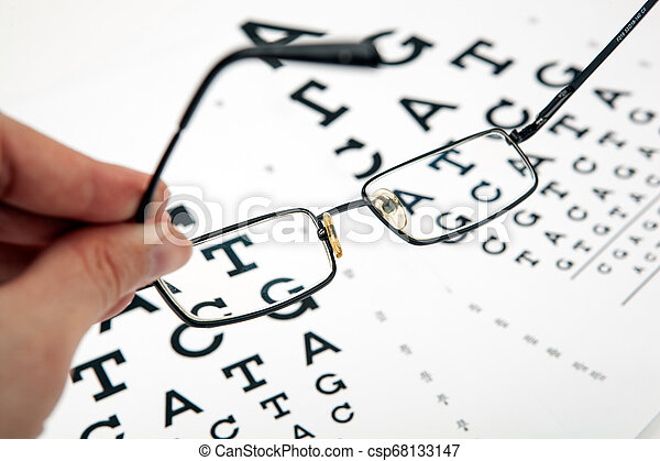 eyeglasses on the table with a font to determine of eyesight English version - csp68133147