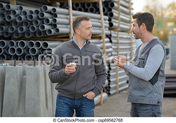 Joven trabajador industrial y gerente fuera de la fábrica - csp69562768
