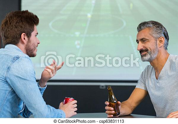 Dos hombres en el bar viendo fútbol - csp63831113
