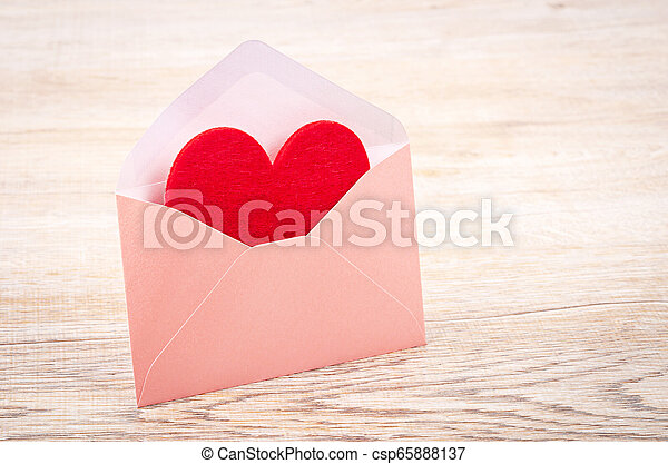 Fabric red heart shape in pink envelupe. - csp65888137