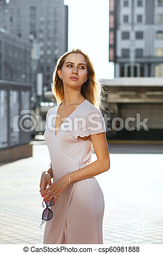 Fabulous blue eyed woman with long hair holding sunglasses, posing in sun glare - csp60981888