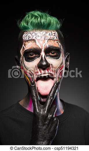 face art man with green hair and bright skull makeup showing tongue halloween makeup dead face in color