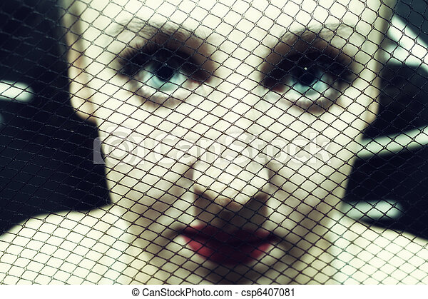 Face of  woman behind the grid - csp6407081